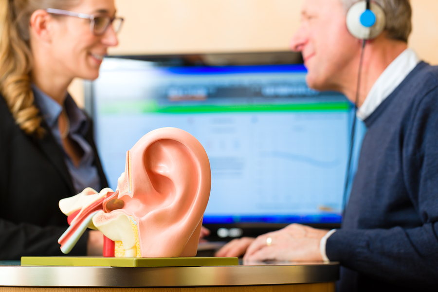 Older man or pensioner with a hearing problem make a hearing tes